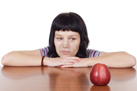 Photo pour Fille regardant une pomme rouge sur fond blanc (foyer dans la pomme ) - image libre de droit