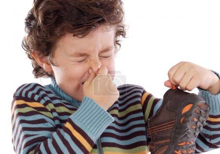 Photo pour Mignon jeune garçon avec chaussure puante poisser son nez - image libre de droit
