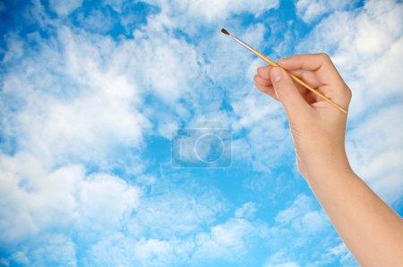 Photo pour Main avec un pinceau dessinant un ciel - image libre de droit
