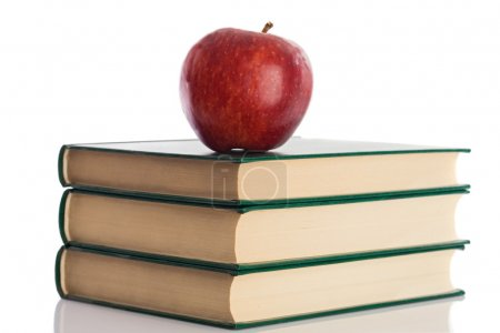 Photo for A red apple on top of three books on a white background - Royalty Free Image