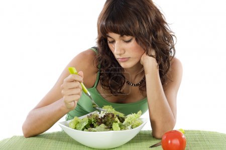 Photo for A sad teen eating salad. Care his diet. - Royalty Free Image
