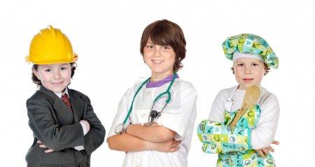 drei Kinder mit Kleidungsstücken verschiedener Berufsgruppen