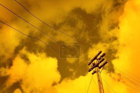 Telegraph pole over sunset sky background