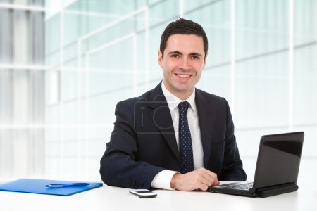Photo for Handsome young business man in blue suit in office with laptop. - Royalty Free Image