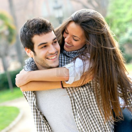 Photo for Close up portrait of attractive young couple piggybacking outdoors. - Royalty Free Image
