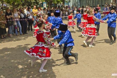 Photo pour Les enfants dansent dans un parc de la ville en costumes cosaques . - image libre de droit