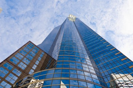 Photo for A Vertical View of a Building with Glass Reflecting the Sky - Royalty Free Image