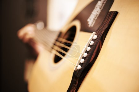 Photo for Close shot of an acoustic guitar and a musician playing it. - Royalty Free Image