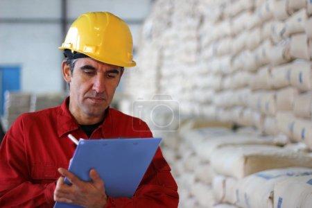 Photo pour Travailleur par écrit les résultats dans l'usine, des sacs en sucrerie - image libre de droit