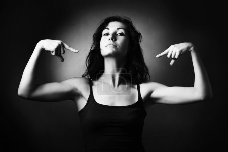 Woman demonstrating her muscles and pointing to he...