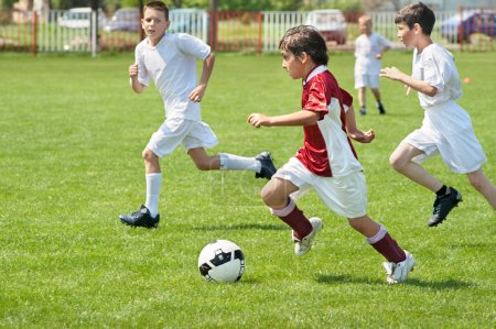 Photo for Boys kicking ball on the sports field - Royalty Free Image