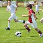 Boys kicking ball on the sports field