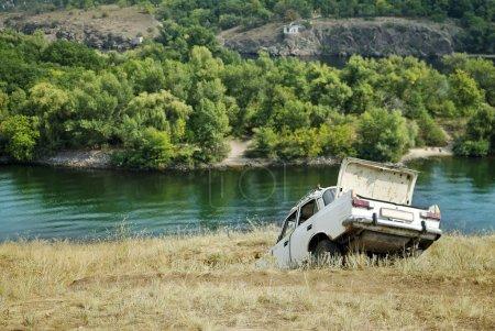 Photo pour Voiture cassée soviétique dans la fosse au bord de la rivière près de l'eau - image libre de droit