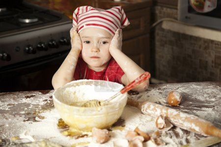 Photo for Little chef in the kitchen wearing an apron and headscarf - Royalty Free Image