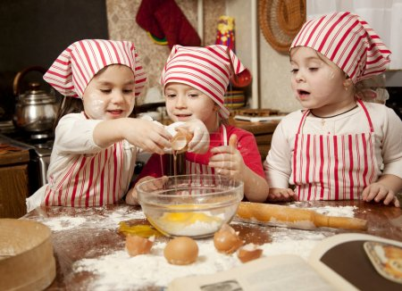 Three little chefs enjoying in the kitchen making big mess. Litt