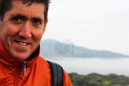 Photo pour Gros plan de séduisant homme d'âge moyen aux cheveux bruns regardant la caméra souriante. En plein air avec la baie de San Francisco en arrière-plan - image libre de droit