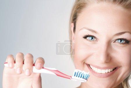 Photo pour Joyeux jeune femme brossant ses dents - image libre de droit