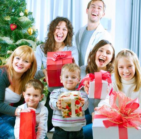 Happy Big family holding Christmas presents at home.Christmas tr