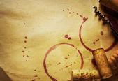 Víno cork, vývrtku a červené víno skvrny na vinobraní papír na pozadí