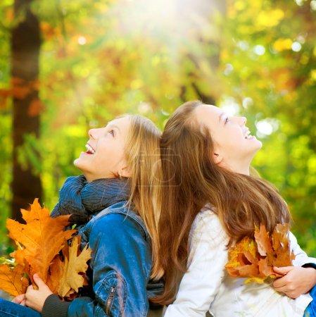 Beautiful Teenage Girls walking in Autumn Park .Outdoor