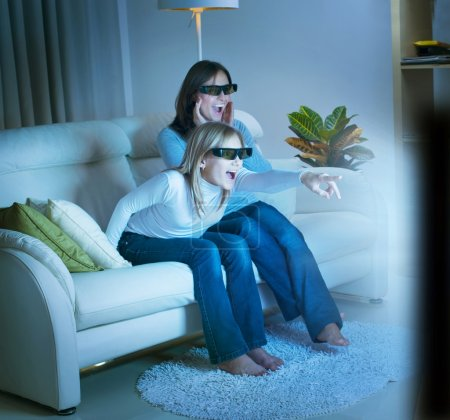 Mother with Daughter watching 3d film on TV