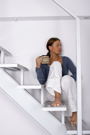 A young woman sitting on the stairs at home...