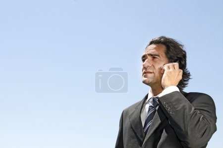 Photo for Businessman answering a call while his colleagues having a discu - Royalty Free Image