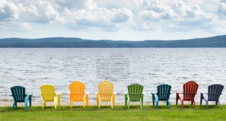Photo for Colorful adirondack chairs are lined up in front of lake, mountains and clouds. - Royalty Free Image