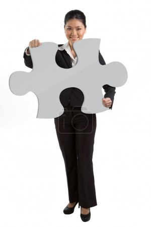 Business woman holding a jigsaw piece.