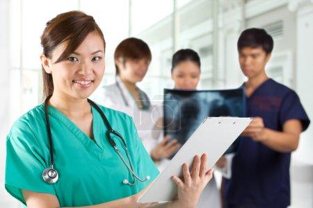 Photo pour Asiatique Femme médecin portant un gommage vert et stéthoscope. Ses collèges sont hors de propos en arrière-plan . - image libre de droit