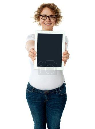 Photo pour Femme montrant l'écran de la tablette à la caméra. Isolé sur blanc - image libre de droit