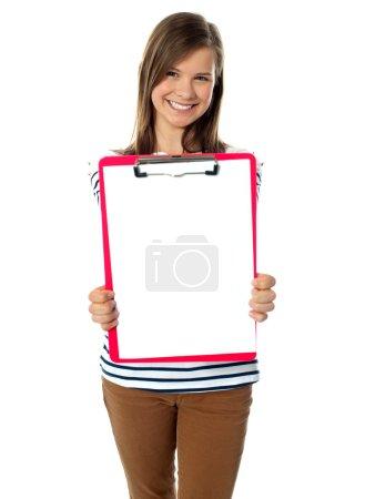 Photo pour Adolescent montrant le papier vierge sur presse-papiers pour caméra - image libre de droit