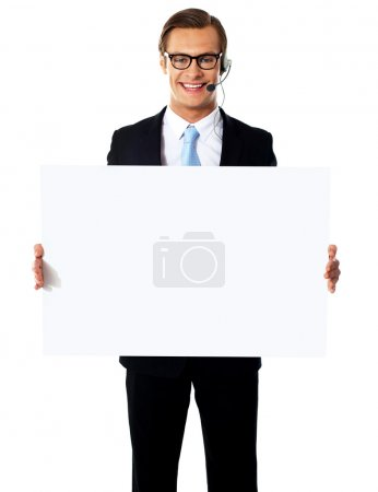 Photo for Smiling customer service male operator holding blank white billboard - Royalty Free Image