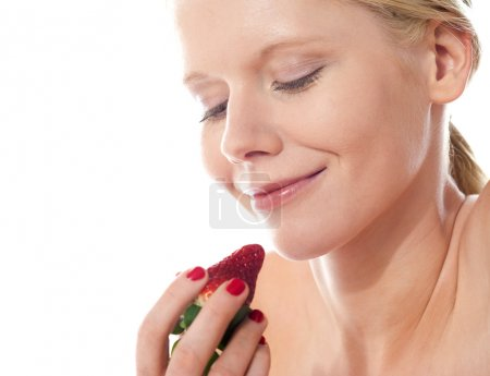 Photo for Attractive young lady holding a strawberry, about to eat - Royalty Free Image