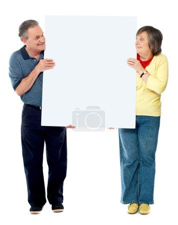 Mature couple presenting blank white billboard