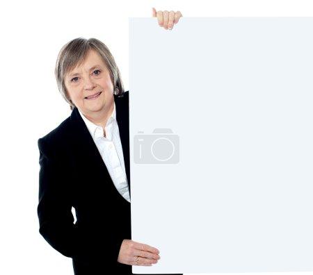 Female executive holding blank whiteboard