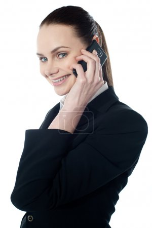 Photo for Female executive talking on mobile and smiling at camera - Royalty Free Image