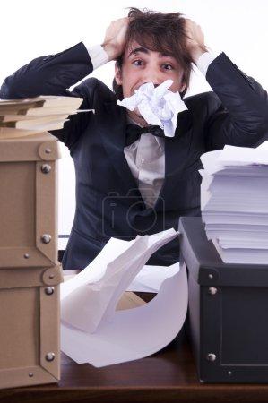 Photo pour Homme d'affaires souligné dans son bureau, de nombreux documents sur le bureau - image libre de droit
