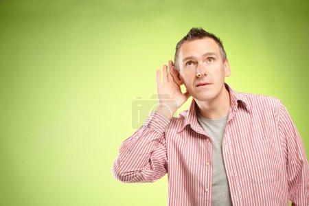 Photo pour Homme écoute avec la main sur l'oreille - image libre de droit