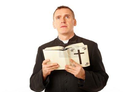 Photo pour Jeune prêtre avec bilbe dans les mains regardant vers le haut - image libre de droit