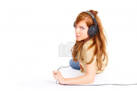 Photo for Girl with headphones laying isolated over white background - Royalty Free Image