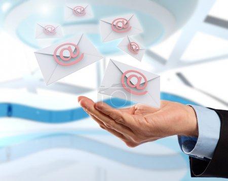 Photo pour Main d'affaires avec des messages électroniques volants, concept de technologie future dans la livraison de lettres . - image libre de droit