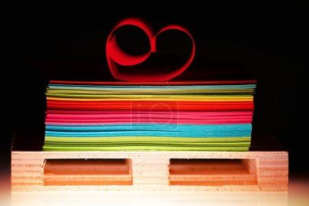 Photo pour Des feuilles de papier colorées et un cœur sur la planche du bas - image libre de droit