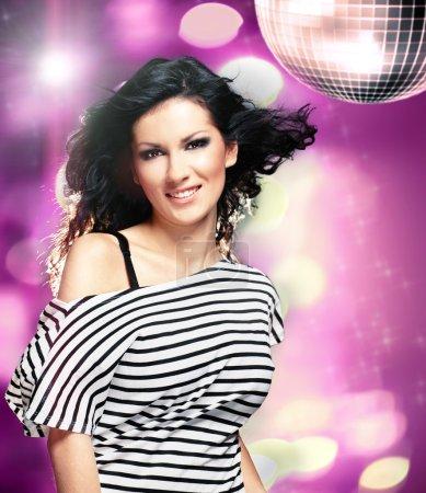 Photo pour Belle femme dans une boîte de nuit avec une grosse boule disco - image libre de droit