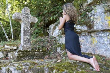 Young woman kneeling in front of a stone cross.