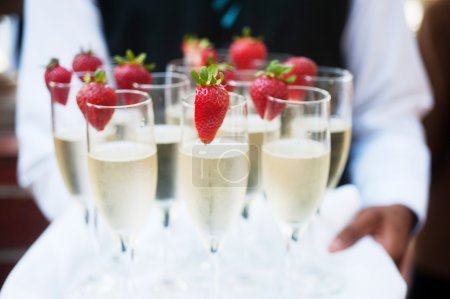Photo for Waiter serving champagne on a tray with strawberries - Royalty Free Image