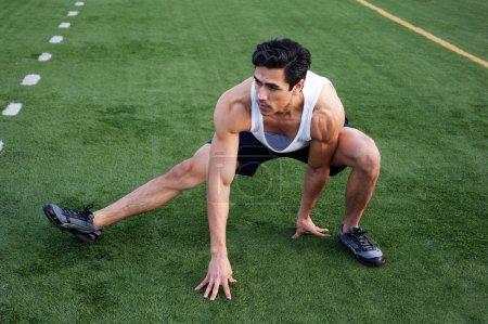 Photo pour Beau, jeune athlète latino s'étirant sur le terrain d'athlétisme - image libre de droit