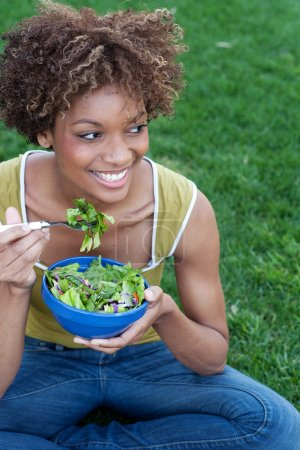 Photo for Pretty African American woman with a healthy salad in a park - Royalty Free Image