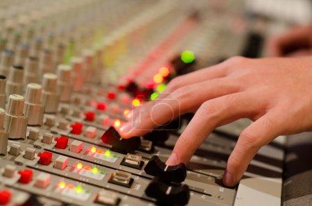 Photo pour Sonner la main de l'ingénieur se déplaçant sur son mixage amplifiée - image libre de droit
