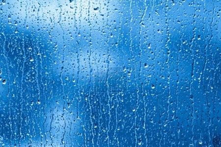 Photo pour Des gouttes de pluie s'accumulent et coulent dans une fenêtre . - image libre de droit